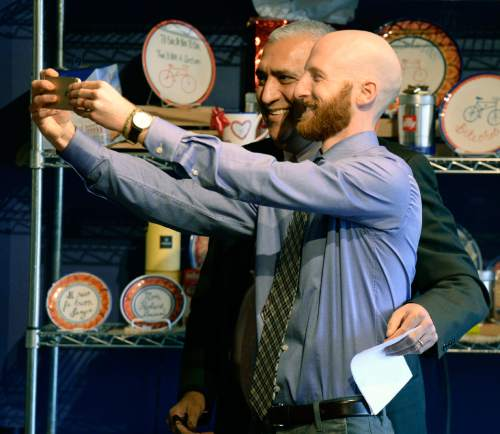 "Al Hartmann  |  The Salt Lake Tribune Derek Kitchen, right, takes a ""selfie"" with Salt Lake County District Attorney Sim Gill at his announcement as candidate for Salt Lake City's District 4 Council Seat at Caputo's across from Pioneer Park Tuesday Feb. 10, 2015. In 2013, Kitchen and his partner, Moudi Sbeity, along with two other gay couples, won their case (Kitchen v. Herbert) in federal court overturning Utah's same-sex marriage ban. It made Utah the 18th state to permit same-sex couples to legally marry. Kitchen is a South Jordan native and the owner and operator of a small business in Salt Lake City. He launched Laziz Foods in 2012. As a resident and business owner, Kitchen said he has a ""unique and valuable"" understanding of the area."