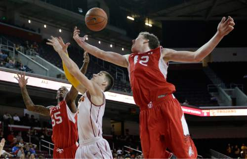 Southern California's Strahinja Gavrilovic, center, of Serbia, fight for a rebound with Utah's Jakob Poeltl, right, of Austria, and Delon Wright during the second half of an NCAA college basketball game, Sunday, Feb. 1, 2015, in Los Angeles. Utah won 67-39. (AP Photo/Jae C. Hong)