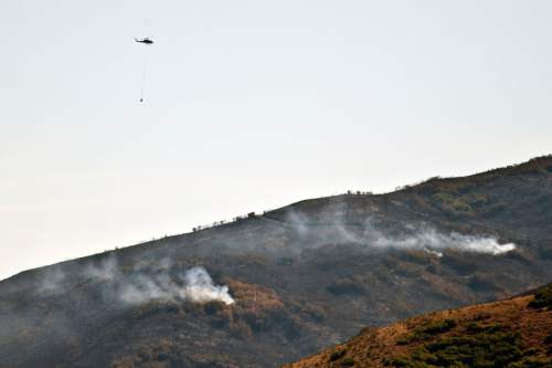 Chris Detrick  |  The Salt Lake Tribune A helicopter with a water bucket flies over the Rockport 5 Fire Thursday August 15, 2013. The Rockport 5 Fire is currently 25 percent contained.