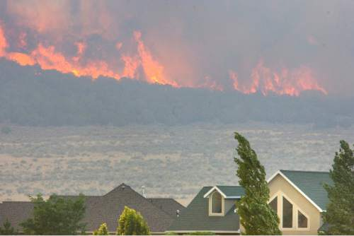 Paul Fraughton | Tribune file photo Wildfires in Utah already have cost $50 million, burning more than 422,000 acres around the state. The Legislature expects to face a $21 million bill and the feds have spent about $34 million. The file photo shows the lightning-caused  Pinion Fire burning behind homes in Eagle Mountain earlier this month.