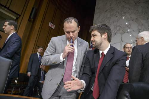 Sen. Mike Lee, R-Utah, center, confers with an aide as the  Senate Judiciary Committee continues for a second day on the confirmation of President Barack Obama's nomination of Loretta Lynch to be attorney general, on Capitol Hill in Washington, Thursday, Jan. 29, 2015. Lynch did not appear at the second and final day of her confirmation hearing, which was designed instead to feature testimony from outside experts, several summoned by Republicans to amplify their criticism of Obama and his current attorney general, Eric Holder. Republicans deride Holder as a liberal firebrand and Obama cheerleader who has failed to cooperate with Congress.   (AP Photo/J. Scott Applewhite)