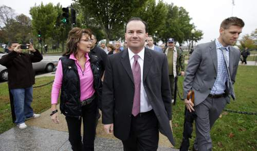 Former Alaska Gov. Sarah Palin, left, and Sen. Mike Lee, R-Utah, center, arrive at a rally at the World War II Memorial on the National Mall in Washington Sunday, Oct. 13, 2013. Leaders in the U.S. Senate have taken the helm in the search for a deal to end the partial government shutdown and avert a federal default. The rally was organized to protest the closure of the Memorial, subsequent to the shutdown, and lack of access to it by World War II veterans, who traveled there on Honor Flight visits. (AP Photo/Alex Brandon)