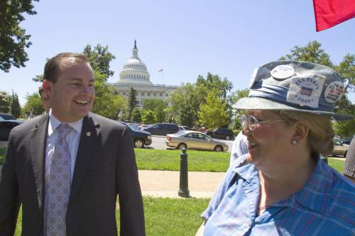 FILE -- In this Wednesday, July 27, 2011 file photo, Sen. Mike Lee, R-Utah, greets a supporter at a Tea Party rally on Capitol Hill in Washington. (AP Photo/Harry Hamburg)