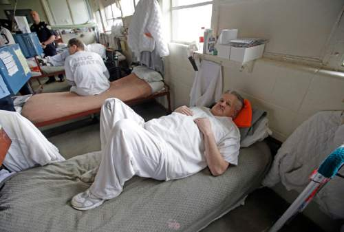 Inmate John Morrell rests on his bed in the geriatric unit during a media tour Thursday, Feb. 26, 2015, at the Utah State Correctional Facility in Draper, Utah. Gov. Gary Herbert said Thursday that he's opposed to the idea of allowing a state commission to pick a location to build a new prison instead of leaving the decision with the Legislature. (AP Photo/Rick Bowmer, Pool)