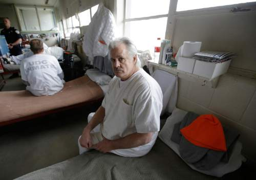Inmate John Morrell sits on his bed in the geriatric unit during a media tour Thursday, Feb. 26, 2015, at the Utah State Correctional Facility in Draper, Utah. Gov. Gary Herbert said Thursday that he's opposed to the idea of allowing a state commission to pick a location to build a new prison instead of leaving the decision with the Legislature. (AP Photo/Rick Bowmer, Pool)