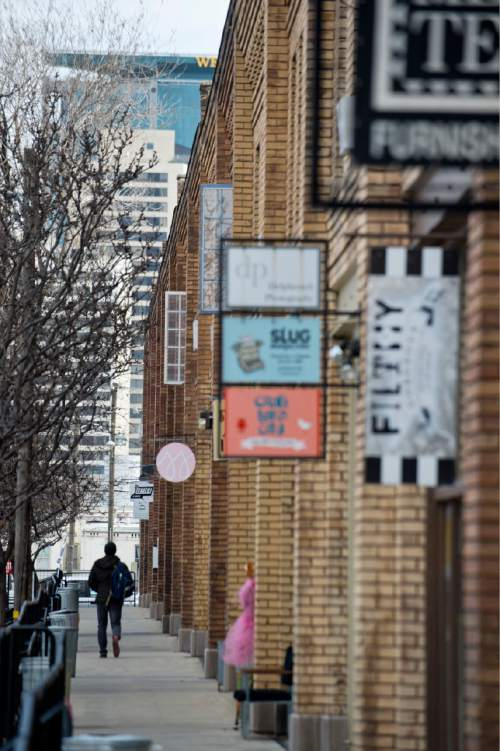Lennie Mahler  |  The Salt Lake Tribune  A man walks along the store fronts on Pierpont Avenue between 300 and 400 West in Salt Lake City, Friday, Feb. 27, 2015. The Eccles Browning Warehouse, a long-time home to small artisan businesses, was sold in January to an out-of-state residential developer.