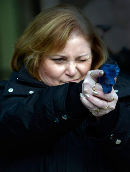 Rick Egan  | The Salt Lake Tribune   Deanna Taylor practices her aim, during a role-playing exercise, as part of a free concealed firearms permit class to Utah educators at the Salt Lake City Library, Friday, January 3, 2014.