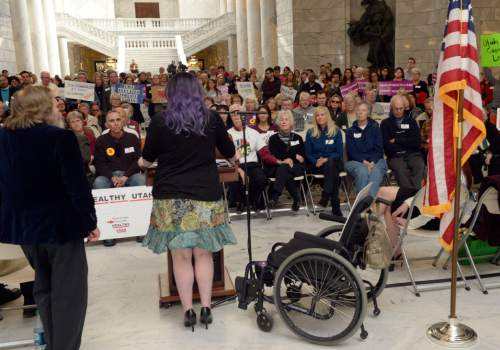 Al Hartmann  |  The Salt Lake Tribune  Stacy Stanford, a Westminster College student, rises for a few minutes from her wheelchair to speak at the Capitol Rotunda on Thursday, March 5, 2015. She and hundreds of citizens and advocates of the governor's plan to expand Medicaid, Healthy Utah, rallied.  She uses a wheelchair after an auto accident resulted in a neurolgical disorder. She is uninsured.
