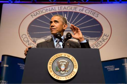 President Barack Obama gestures that he is listening to the crowd as he speaks at the National League of Cities annual Congressional City Conference in Washington, Monday, March 9, 2015. Targeting stagnant wages in an otherwise improving economy, the president is calling on employers, educational institutions and local governments to ramp up training and hiring of high-technology in an effort to drive up higher-income employment. (AP Photo/Jacquelyn Martin)