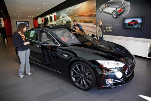 FILE - In this Saturday, Jan. 3, 2015 photo, shoppers check out the Tesla model S at the Tesla showroom at the the Third Street Promenade in Santa Monica, Calif.  (AP Photo/Richard Vogel)