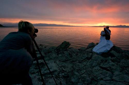Rick Egan  |  Tribune file photo Susan Adams takes advantage of the sunset as she shoots wedding photos of Emily Mecham and Brian Shaw at the Great Salt Lake in 2013. More than twenty percent of Utahns have been married more than once.