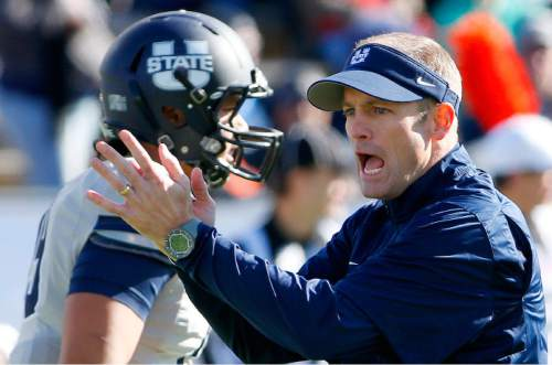 Utah State head coach Matt Wells cheers along with players prior to a New Mexico Bowl college football game against UTEP, Saturday, Dec. 20, 2014, in Albuquerque, N.M. (AP Photo/Ross D. Franklin)