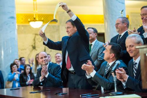 Chris Detrick  |  The Salt Lake Tribune After signing it, Gov. Gary Herbert holds up a copy of SB296, which gives statewide non-discrimination protections to the gay and transgender community, while providing safeguards for religious liberty, in the rotunda of the State Capitol Building, Thursday March 12, 2015.