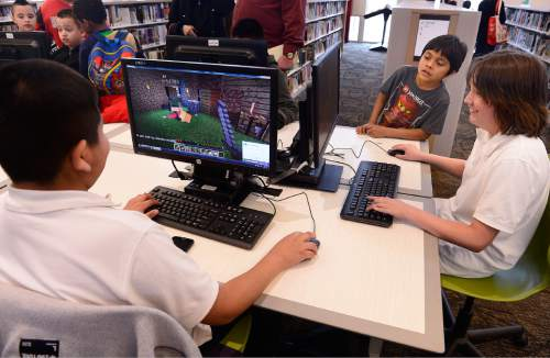 Scott Sommerdorf   |  The Salt Lake Tribune Jesus Mota, left, plays Minecraft along with Joe Garcia, right, as Anthony Arrinda Lopez watches in the background at the Glendale Public Library, Thursday, March 12, 2015.