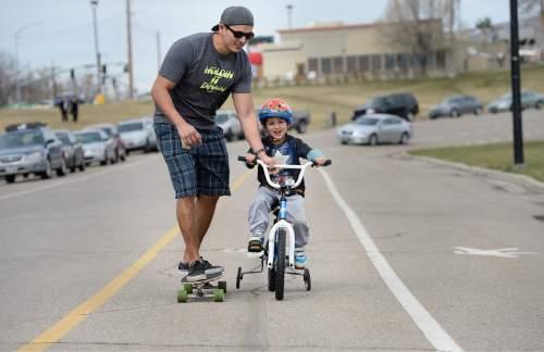 Scott Sommerdorf      The Salt Lake Tribune Ivanov Estrada teaches his son Sabastian how to ride a bike while on a skateboard at Sugarhouse Park, Sunday, March 15, 2015.