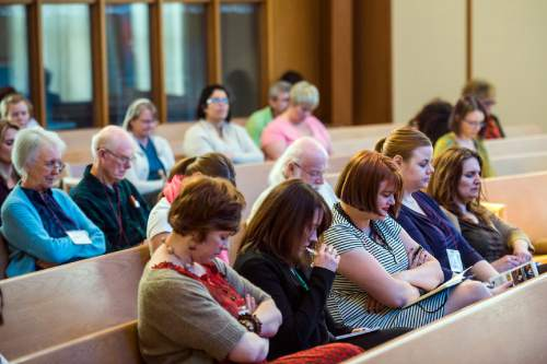 "Chris Detrick  |  The Salt Lake Tribune Attendees pray during the Sunstone Symposium at the Community of Christ Church Saturday March 14, 2015. This ""Theology from the Margins Conference"" was for Mormons to reflect on their experiences being people of color in the LDS Church."