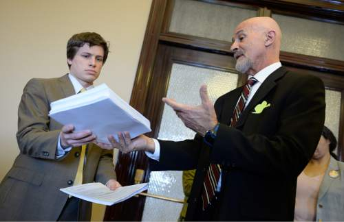 Francisco Kjolseth  |  The Salt Lake Tribune  MoveOn member Ralph Dellapiana, right, who is also the director of Utahns for Alternatives to the Death Penalty, delivers 6,200 petitions to Constituent Services Director Austin Cox, who accepted them on behalf of Gov. Gary Herbert on Tuesday, March 17, 2015. Utah residents delivered the petitions, many from across the world and Utah, calling on the governor to veto execution by firing squad legislation.