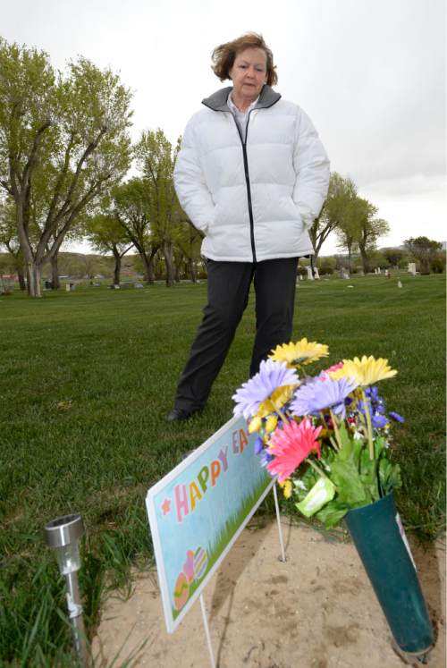 Al Hartmann  |  Tribune file photo Midwife Donna Young looks at a grave marker of a stillborn child in Rock Point Cemetery in Maeser just north of Vernal. She started noticing a higher than usual amounts of stillborn and newborn deaths in the area the past few years. One corner of the cemetery has several small markers for stillborn and newborn deaths.