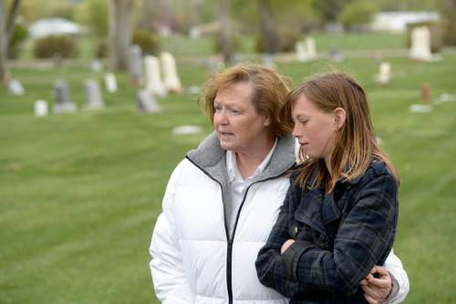 (Al Hartmann  |  Tribune file photo) Midwife Donna Young and her daughter Holt, look at a grave markers of stillborn and newborn children in Rock Point Cemetery in Maeser just north of Vernal in May 2014. Young started noticing a higher than usual number of stillborn and newborn deaths in the area the past few years. One corner of the cemetery has several small markers for stillborn and newborn  deaths.