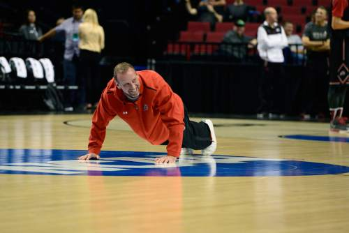Scott Sommerdorf   |  The Salt Lake Tribune Utah Utes head coach Larry Krystkowiak does push-ups on the NCAA logo at center court during the Utah practice session at the Moda Center in Portland, Wednesday, March 18, 2015.