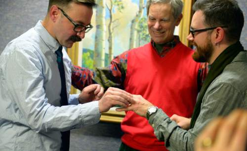 Keith Johnson | The Salt Lake Tribune  Mark Hofeling, left, exchanges rings with new husband Jesse Walker while being married by Salt Lake City Mayor Ralph Becker outside the Salt Lake County clerks office, Friday, December 20, 2013. A federal judge in Utah Friday struck down the state's ban on same-sex marriage, saying the law violates the U.S. Constitution's guarantees of equal protection and due process.
