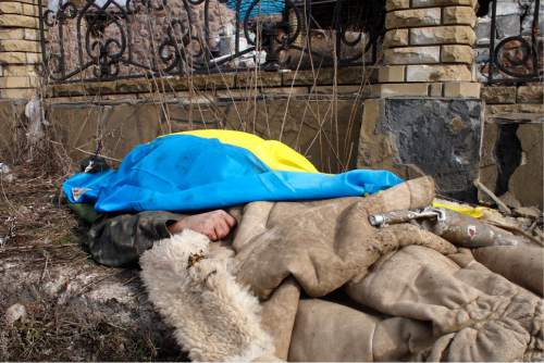 A body of a government soldier lies by the side of the road and is covered by a Ukrainian national flag in the east Ukraine town of Debaltseve on Thursday, Feb. 19, 2015. After weeks of relentless fighting, the embattled Ukrainian rail hub of Debaltseve fell Wednesday to Russia-backed separatists, who hoisted a flag in triumph over the town. The Ukrainian president confirmed that he had ordered troops to pull out and the rebels reported taking hundreds of soldiers captive. (AP Photo/ Peter Leonard)