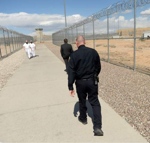 Al Hartmann  |  The Salt Lake Tribune  Inmates and corrections officers walk through a fenced corridor at the Central Utah Correctional Facility in Gunnison Monday March 23, 2015.