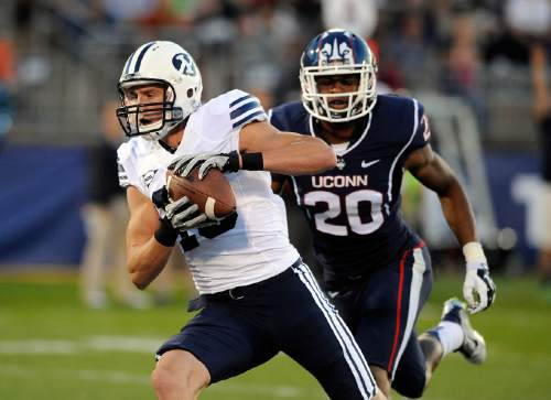 BYU wide receiver Mitch Mathews (10) makes a touchdown reception while being covered by Connecticut safety Obi Melifonwu (20) during the first half of an NCAA college football game in East Hartford, Conn., Friday, Aug. 29, 2014. (AP Photo/Fred Beckham)