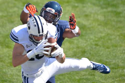 Chris Detrick  |  The Salt Lake Tribune Virginia Cavaliers safety Brandon Phelps (21) defends Brigham Young Cougars wide receiver Mitch Mathews (10) as Mathews can't make a potential touchdown catch during the game at LaVell Edwards Stadium Saturday September 20, 2014.  Virginia is winning the game 16-13 at halftime.