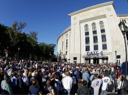 Fans line up outside Gate 4 at Yankee Stadium for a free Mariano Rivera bobblehead doll before the Yankees' baseball game against the Tampa Bay Rays, Tuesday, Sept. 24, 2013, in  New York. The Mormon Tabernacle Choir is scheduled to perform at the stadium prior to the Yankees-Rays game on July 3, 2015.  (AP Photo/Kathy Willens)