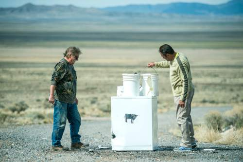 Chris Detrick  |  The Salt Lake Tribune Robert Kirby and friend Sonny inspect the damage after they fired a pool ball out of a cannon into paint buckets in Rush Valley Saturday March 21, 2015.