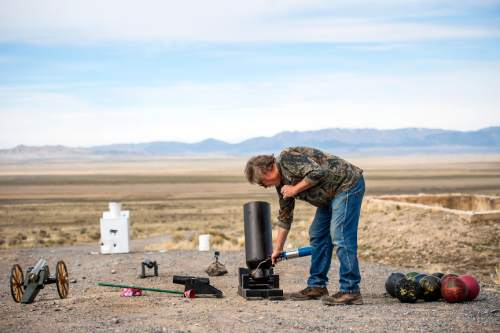 Chris Detrick  |  The Salt Lake Tribune Robert Kirby lights the fuse on a cannon to shoot out a bowling ball in Rush Valley Saturday March 21, 2015.