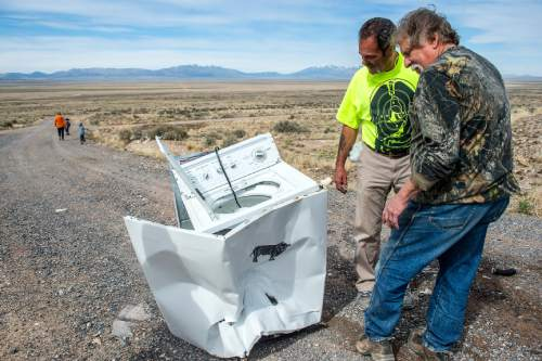Chris Detrick  |  The Salt Lake Tribune Robert Kirby and friend Sonny inspect the damage of the washing machine after shooting it with a bowling ball fired from a cannon in Rush Valley Saturday March 21, 2015.