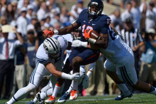 Chris Detrick  |  The Salt Lake Tribune Virginia Cavaliers wide receiver Donovan Dowling (19) is tackled by Brigham Young Cougars linebacker Alani Fua (5) during the game at LaVell Edwards Stadium Saturday September 20, 2014.  Virginia is winning the game 16-13 at halftime.