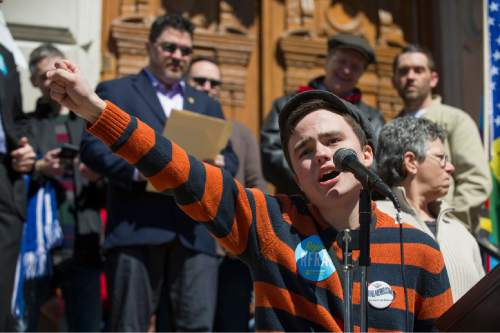 Jackson Blanchard, 18, of Indianapolis, leads the crowd in a chant during the event. Thousands of opponents of Indiana Senate Bill 101, the Religious Freedom Restoration Act, gathered on the lawn of the Indiana State House to rally against that legislation Saturday, March 28, 2015. Indiana's law has been widely criticized by businesses and organizations around the country. (AP Photo/Doug McSchooler)