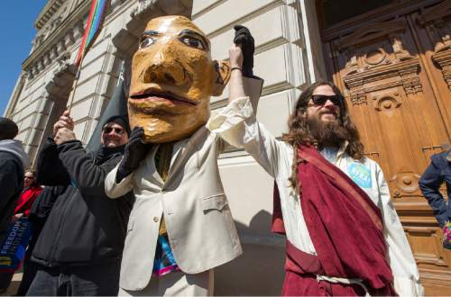 """A pair of impersonators take part in the cheering during the event. Thousands of opponents of Indiana Senate Bill 101, the Religious Freedom Restoration Act, gathered on the lawn of the Indiana State House to rally against that legislation Saturday, March 28, 2015.  Republican Gov. Mike Pence signed a bill Thursday prohibiting state laws that """"substantially burden"""" a person's ability to follow his or her religious beliefs. (AP Photo/Doug McSchooler)"""