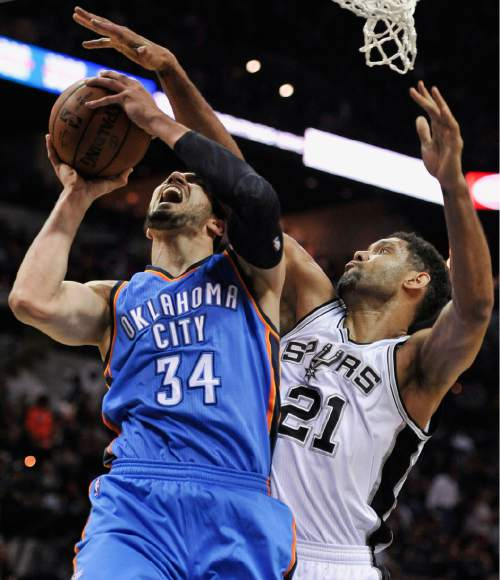 Oklahoma City Thunder forward Enes Kanter (34), of Turkey, is defended by San Antonio Spurs forward Tim Duncan during the first half of an NBA basketball game, Wednesday, March 25, 2015, in San Antonio. (AP Photo/Darren Abate)