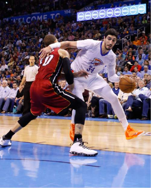 Oklahoma City Thunder center Enes Kanter (34) drives to the basket around Miami Heat forward Michael Beasley (30) during the fourth quarter of an NBA basketball game in Oklahoma City, Sunday, March 22, 2015. Oklahoma City won 93-75. (AP Photo/Alonzo Adams)