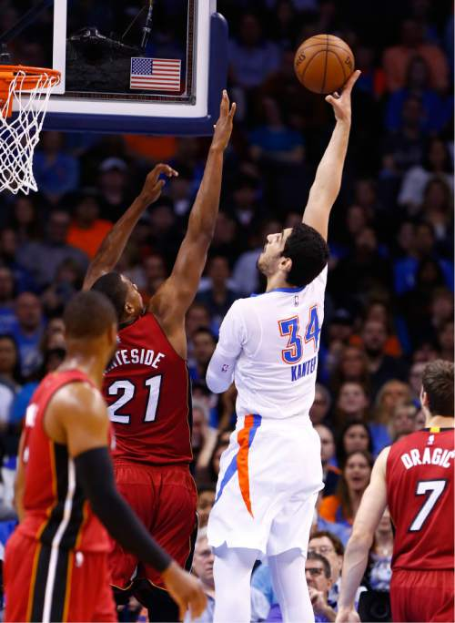Oklahoma City Thunder center Enes Kanter (34) shoots as Miami Heat center Hassan Whiteside (21) defends during the first quarter of an NBA basketball game in Oklahoma City, Sunday, March 22, 2015. (AP Photo/Alonzo Adams)
