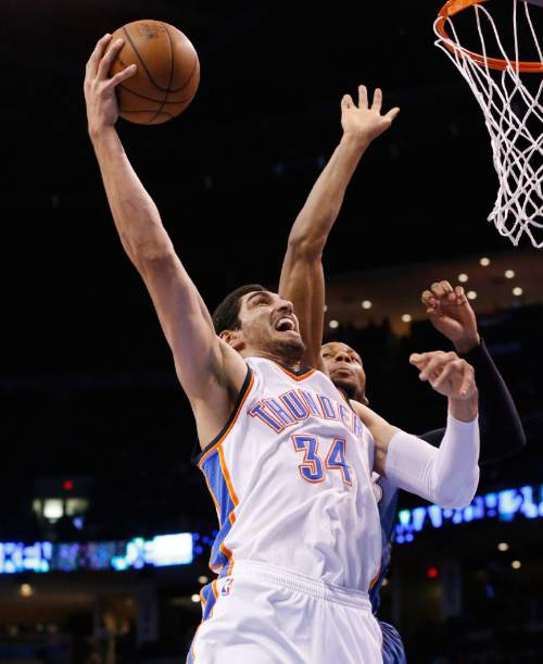 Oklahoma City Thunder center Enes Kanter (34) shoots in front of Minnesota Timberwolves forward Adreian Payne during the third quarter of an NBA basketball game in Oklahoma City, Friday, March 13, 2015. Oklahoma City won 113-99. (AP Photo/Sue Ogrocki)