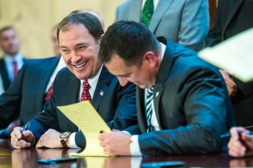 Chris Detrick  |  The Salt Lake Tribune Gov. Gary Herbert smiles as he and House Speaker Greg Hughes sign SB296 at the Utah State Capitol Thursday March 12, 2015.