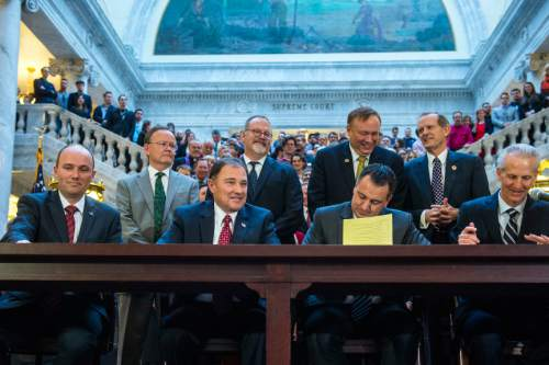 Chris Detrick  |  The Salt Lake Tribune Utah Lt. Gov. Spencer Cox,  Gov. Gary Herbert,  House Speaker Greg Hughes, and Senate President Wayne Niederhauser sign SB296 at the Utah State Capitol Thursday March 12, 2015.