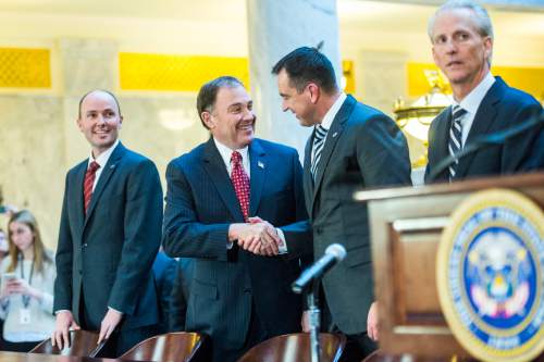 Chris Detrick  |  The Salt Lake Tribune Gov. Gary Herbert and House Speaker Greg Hughes shake hands during the signing ceremony for SB296 at the Utah State Capitol Thursday March 12, 2015.