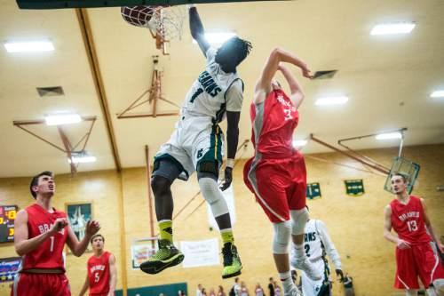 Chris Detrick  |  The Salt Lake Tribune Kearns' Bushmen Ebet (1) dunks past Bountiful's Jake Lasalle (3) during the game at Kearns High School Friday January 30, 2015.