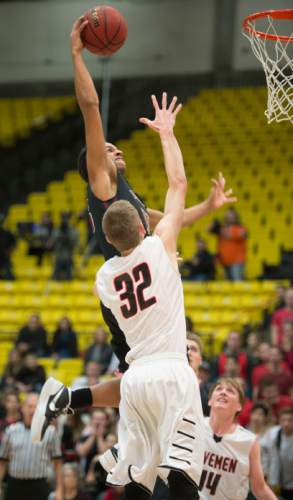 Steve Griffin  |  The Salt Lake Tribune  Lone Peak's Frank Jackson leaps into the air as he throws down a dunk over American Fork's Spencer Johnson during game between American Fork and Lone Peak at UVU UCCU Arena in Provo, Tuesday, February 10, 2015.