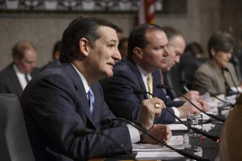 Senate Armed Services Committee member Sen. Ted Cruz, R-Texas, left, joined by Sen. Mike Lee, R-Utah, center, poses questions to Ashton Carter, President Barack Obama's choice to be defense secretary, as he goes before the committee for confirmation to replace Chuck Hagel as Pentagon chief, Wednesday, Feb. 4, 2015, on Capitol Hill in Washington.    (AP Photo/J. Scott Applewhite)