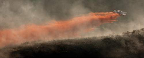 Jeremy Harmon  |  The Salt Lake Tribune  A plane dumps retardant on the fire in the foothills above Herriman on Friday, June 29, 2012.