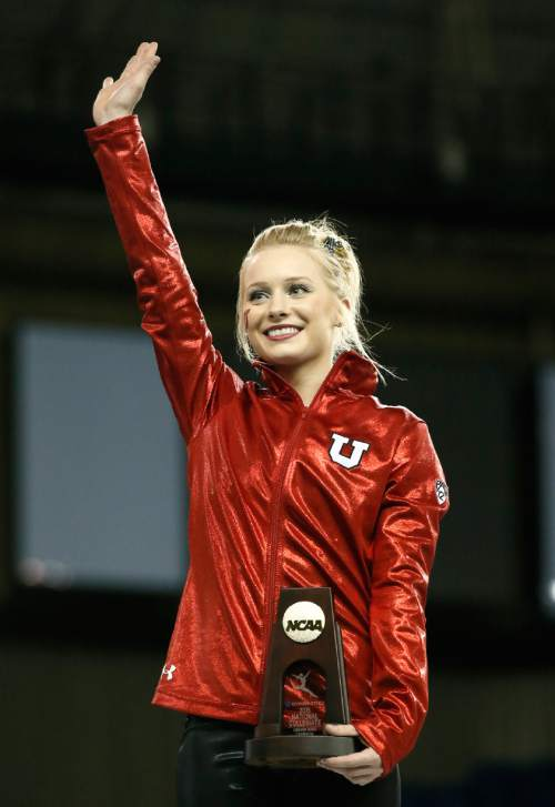 Utah's Georgia Dabritz acknowledges cheers after being introduced as the uneven parallel bars national champion during the NCAA women's gymnastics championships Sunday, April 19, 2015, in Fort Worth, Texas. (AP Photo/Tony Gutierrez)