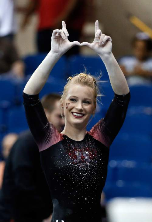 "Utah's Georgia Dabritz celebrates by gesturing the ""U"" after competing on the uneven parallel bars during the NCAA women's gymnastics championships Sunday, April 19, 2015, in Fort Worth, Texas. Dabritz won the national title on the event. (AP Photo/Tony Gutierrez)"