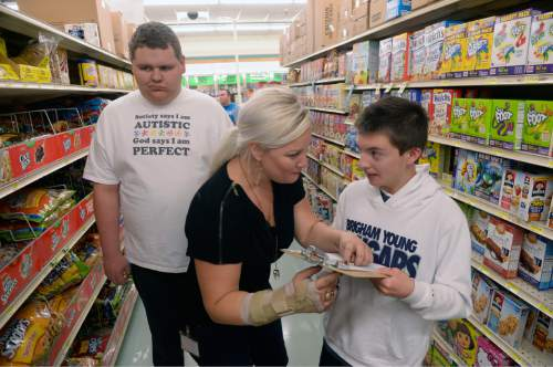 Al Hartmann  |  The Salt Lake Tribune  Teens from the Carmen B. Pingree Autism Center of Learning accompany teacher Markell McCubbin of the adolescent program on a shopping trip to Ream's Food Store in Salt Lake City Tuesday April 14, 2015. McCubbin helps Sam handle the clipboard with the group's shopping list, as Gavynn is alongside. The students buy, sort and distribute food items with the help of teachers. It's part of a curriculum designed to prepare the students for adulthood.